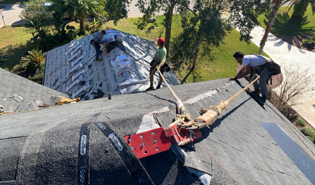 StormForce crew on top of a residential home working on a roof repair.